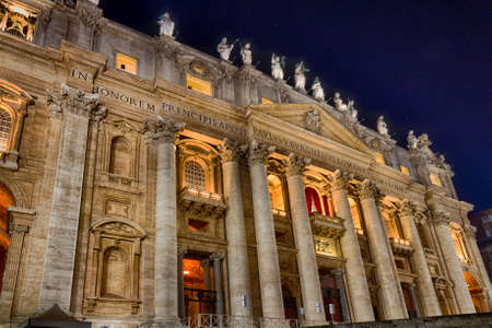 st  peter's basilica pope: Night view of facade of church in Vatican City with Holy doors, columns and statue