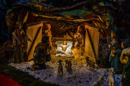 Statues in a Christmas Nativity scene, the Blessed Virgin Mary and Saint Joseph watch over the Holy Child Jesus in a manger in the straw as the ox and the donkey are warming