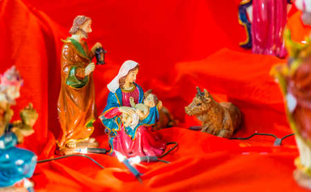 jesus mary joseph: Statues in a Christmas Nativity scene, the Blessed Virgin Mary and Saint Joseph watch over the Holy Child Jesus in a manger in the straw while the ox and the donkey are warming air