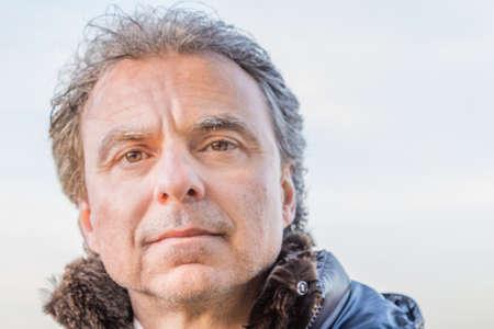 Mittleren Alters kaukasischen Mann mit grauem Haar in der schwarzen Daunenjacke gekleidet