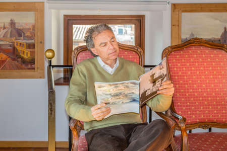 parlor: Caucasian middle-aged man reading a magazine sitting comfortably in a vintage parlor Stock Photo