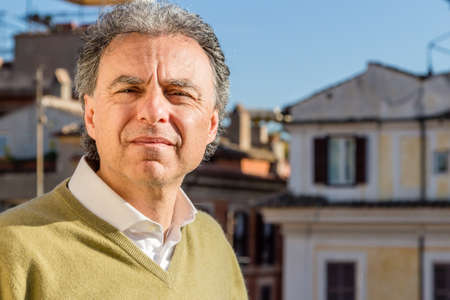 uncomfortable: middle-aged man in green polo with the palaces of Rome in the background squints uncomfortable with excessive light of the sun Stock Photo