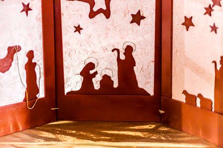 silhouette of a Christmas Nativity scene, the Blessed Virgin Mary and Saint Joseph watch over the Holy Child Jesus