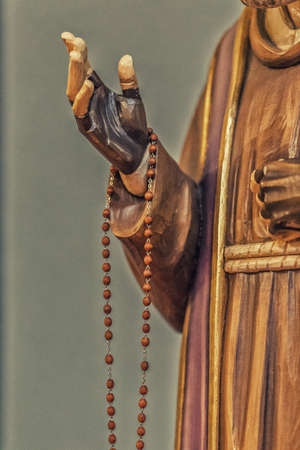 stigmata: detail of a wood carved statue of Saint Father Pius with his gloved hands to cover the stigmata while holding a rosary