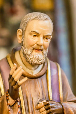 pious: detail of a wood carved statue of Saint Father Pius with his gloved hands to cover the stigmata while holding a rosary