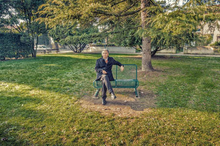 blue grey coat: Middle-aged man with gray hair at the public gardens dressing a black coat and a light blue shirt smiles while sitting on a bench