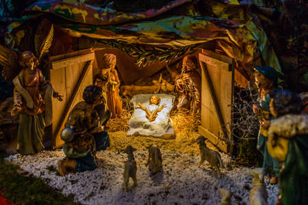 pesebre: Statues in a Christmas Nativity scene, the Blessed Virgin Mary and Saint Joseph watch over the Holy Child Jesus in a manger in the straw as the ox and the donkey are warming