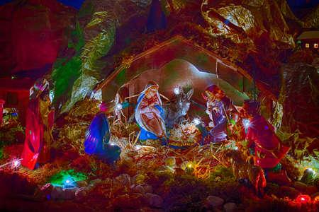 pesebre: Estatuas en una escena de la natividad, la Virgen María y San José velan por el Santo Niño Jesús en un pesebre en la paja como el buey y el asno se están calentando Foto de archivo