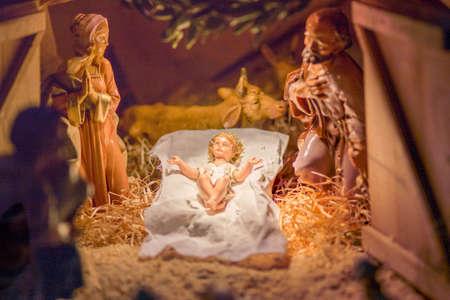 pesebre: Estatuas en una escena de la natividad de la Navidad, la Sant�sima Virgen Mar�a y San Jos� velan por el Santo Ni�o Jes�s en un pesebre en la paja, mientras que el buey y el asno se est�n calentando el aire Foto de archivo