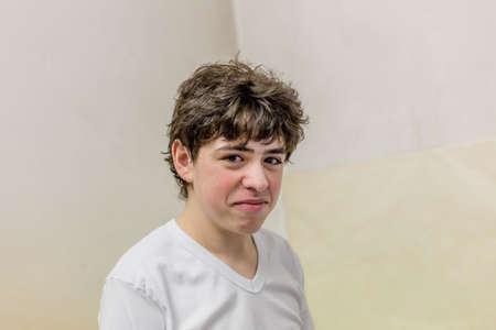 disheveled: boy disheveled and slightly bent in white tshirt makes faces