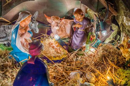 pesebre: Estatuas en una escena de la natividad, la Virgen Mar�a y San Jos� velan por el Santo Ni�o Jes�s en un pesebre en la paja como el buey y el asno se est�n calentando Foto de archivo