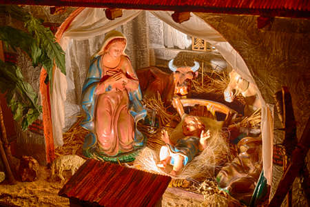 joseph: Statues in a Christmas Nativity scene, the Blessed Virgin Mary and Saint Joseph watch over the Holy Child Jesus in a manger in the straw as the ox and the donkey are warming