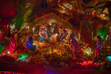 jesus mary joseph: Statues in a Christmas Nativity scene, the Blessed Virgin Mary and Saint Joseph watch over the Holy Child Jesus in a manger in the straw as the ox and the donkey are warming while the three wise men bring gifts of gold, frankincense and myrrh