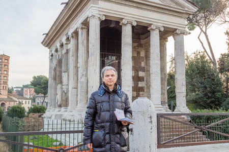 peripteral: modern man with map near  ancient rectangular, tetrastyle, pseudo-peripteral Roman temple of Ionic order in Rome, Italy, dated back to IV century Before Christ