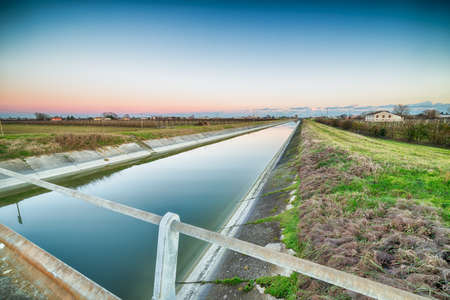 bridge on artificial water canal to irrigate the cultivated fields in the countryside of Emilia Romagna in Italy