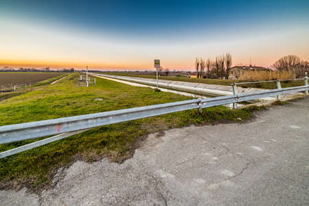 irrigate: bridge on artificial water canal to irrigate the cultivated fields in the countryside of Emilia Romagna in Italy