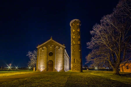 oldest: night view of the brick walls of an old Catholic church with one of the oldest  belltowers in Italy