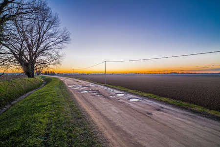 flanked: dirt country road passes through cultivated fields plowed by potholes and puddles of freezing water flanked by an irrigation canal