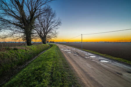 dirt country road passes through cultivated fields plowed by potholes and puddles of freezing water flanked by an irrigation canal