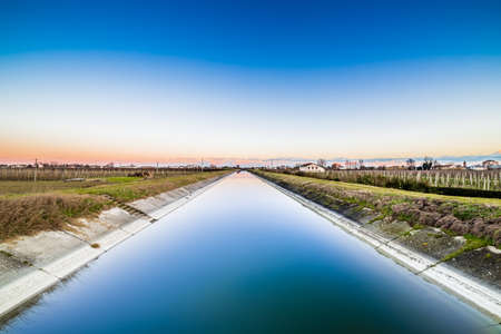 irrigate: artificial water canal to irrigate the cultivated fields in the countryside of Emilia Romagna in Italy Stock Photo