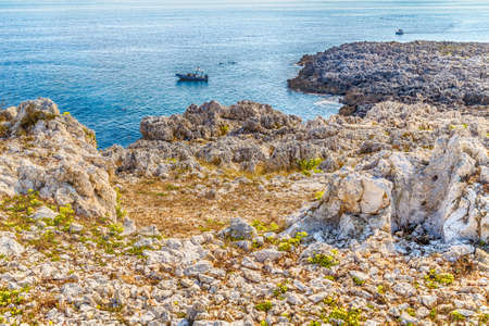 the blue sea and the wild, rocky coast of Salento close to the Tower of the Serpent, ancient watchtower near Otranto in Puglia in Italy.