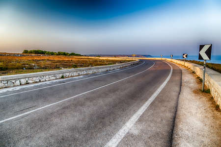 beachfront: curve on asphalt road with centreline in Italy, with warning road signs on the beachfront Stock Photo