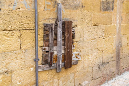 nailed: ruined window made of boards nailed on old wall