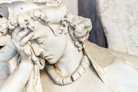face close up: dusted statue of crying angel holding his head while tears is flowing on nose Stock Photo