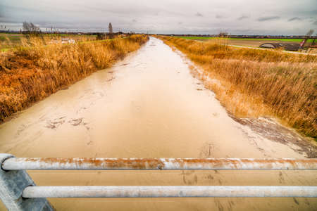 waters: Muddy waters of a swollen river in the countryside Stock Photo