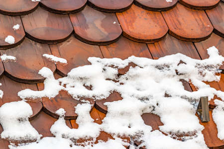 winter thaw: snow thaws on the tiles of a roof