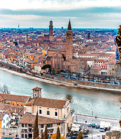 romeo and juliet: panorama of the Adige River as it passes through the houses and historical buildings of Verona in Italy, known as romantic city of love because Romeo and Juliet by Shakespeare was set here