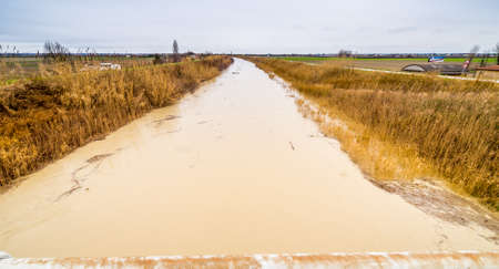 Swollen: Muddy waters of a swollen river in the countryside Stock Photo