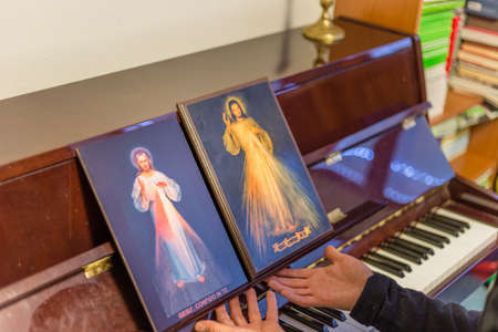 the merciful: the two icons of the Merciful Jesus on a piano as if they were musical scores in front of pianist: the Italian sentence on the bottoms means Jesus, I Trust in you
