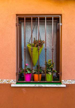 ventana con reja de hierro y fucsia, naranja y verde macetas de