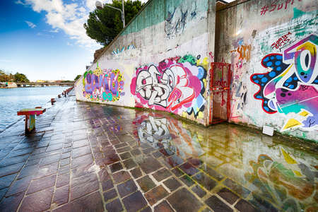 bollards: the Rimini canal port with graffiti, pigeons, bollards and moored boats, modern buildings and old houses