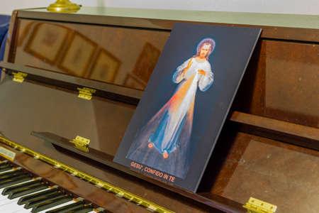 frase: el icono de Jesús Misericordioso en un piano en lugar de las puntuaciones: frase italiano escrito en la parte inferior que significa Jesús en Ti confío