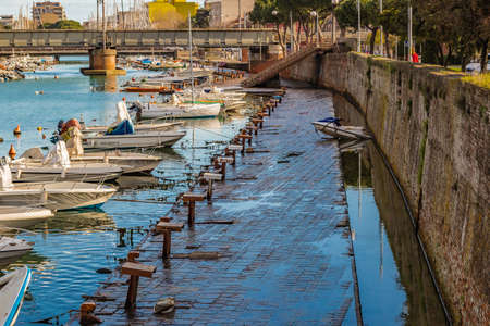mooring bollards: strange mooring boat near rusty cleats on the port channel of the city of Rimini in Emilia Romagna, Italy