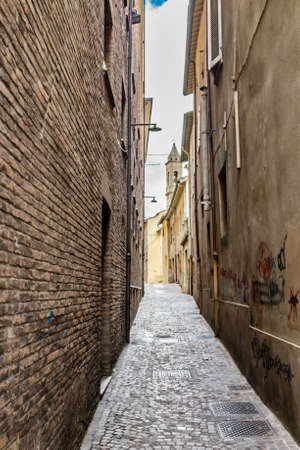 narrow alleys between the vertiginous walls of ancient buildings in the historic center of Rimini in Italy