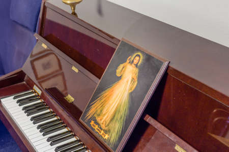 scores: the Merciful Jesus icon on a piano in place of scores: italian sentence written on the bottom meaning Jesus I trust in You