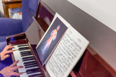 the merciful: the Merciful Jesus icon on scores  while pianist is playing the piano: italian sentence written on the bottom means Jesus I trust in You