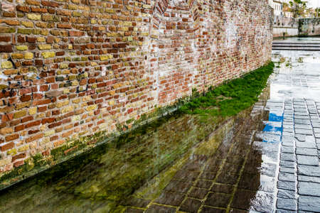 reflected: old brick wall reflected in a puddle