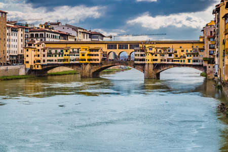 peacefully: historic buildings overlooking the Arno river that flows peacefully under the arches of the old bridge of Florence on a bright winter day