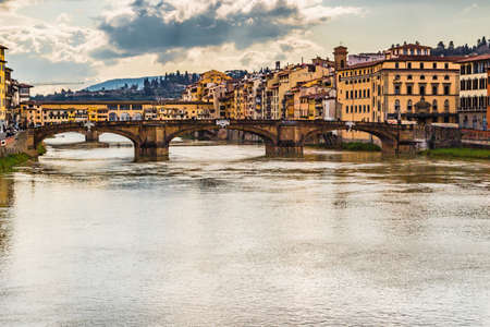 peacefully: historic buildings overlooking the Arno river that flows peacefully under the arches of the ancient bridge of Florence on a bright winter day