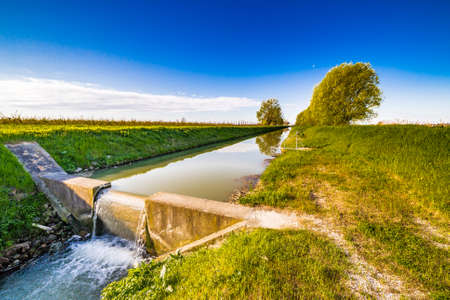 Modern irrigation canal that runs through the cultivated fields of Emilia Romagna in Italy