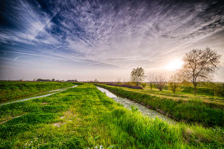 romagna: two parallel irrigation canals run through the fields in the countryside of Romagna