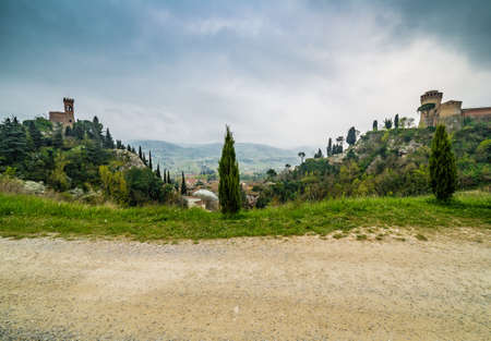 bordered: country dirt road bordered by cypress trees next to the fortress and the clock tower of the village of Brisighella in Italy