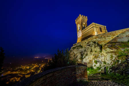 crenellated: night view of crenellated clock tower above the roofs in the old town of Brisighella in the valley nestled among the hills of Emilia Romagna in Italy Stock Photo