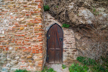 scraped: old wooden medieval round door of ruined and  scraped wall Stock Photo