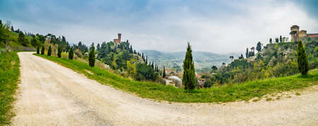 bordered: country dirt road bordered by cypress trees next to the clock tower of the village of Brisighella in Italy Stock Photo