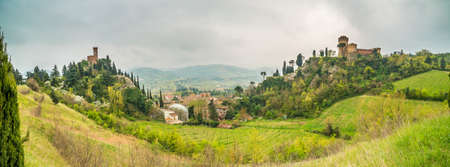 the green countryside around the fortress and the clock tower overlooking Brisighella in the Emilia Romagna in Italy